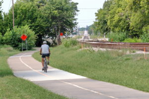 Person riding bike on bike trail next to the new TEXRail train track