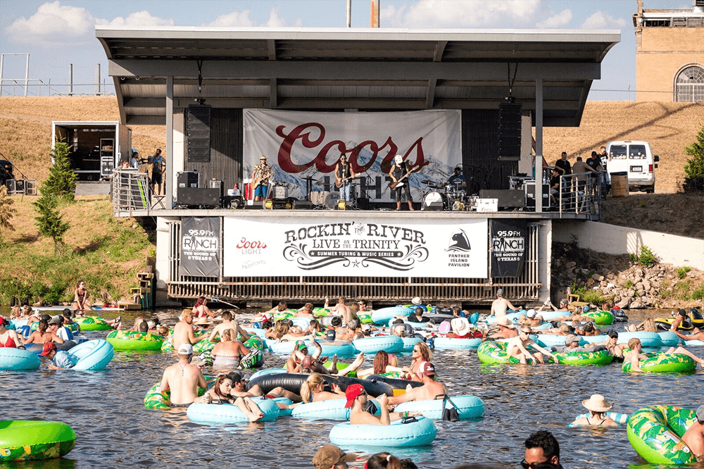 people tubing on the trinity river in front of band at panther island pavilion